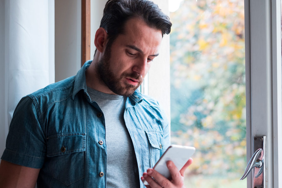 Image of Sad man holding phone alone at home